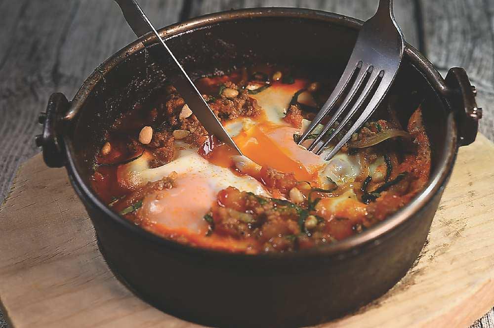 →〈夏卡蘇卡〉是用小鐵鍋將大量番茄、洋蔥、辣椒、大蒜炒香,再加入摩洛哥香料與番茄混合,最後打入兩顆水波蛋,撒上烤至香酥的松子及杏仁片。圖/姚舜